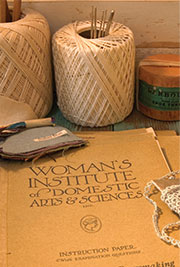 Thread, needles, and other needlework supplies, with an open book—Woman's Institute of Domestic Arts and Sciences—Merit Badge Requirements